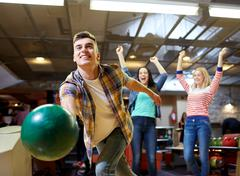 Stock Photo of happy young man throwing ball in bowling club