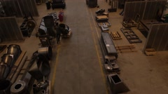 Man carrying cart with material in an industrial shed. Stock Footage