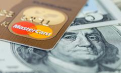Photo of Mastercard credit card with american dollars - stock photo
