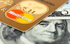 Photo of Mastercard credit card with american dollars Stock Photos