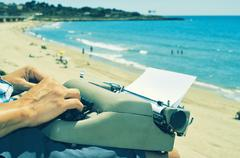 young man typewriting on the beach - stock photo