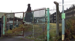 Old industrial building bottle kiln behind rusty green gate at Stoke Stock Footage