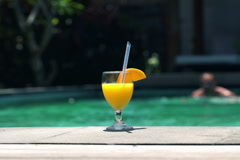 Tropical drink by pool with swimming man NTSC Stock Footage