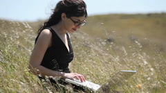 A woman using a laptop sits in a field. - stock footage