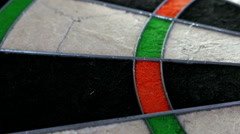 Close dolly on a dart board revealing the bull's eye with three darts, 4K Stock Footage