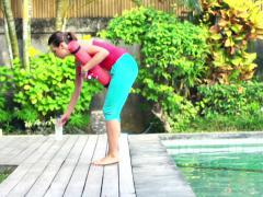 Young woman bringing equipment for exercising in garden by swimming pool NTSC Stock Footage