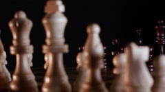 Chessboard and chess pieces on black background Stock Footage