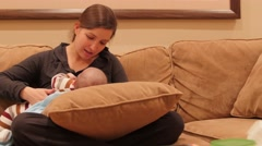 Young mother nursing her newborn baby boy on couch Stock Footage