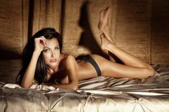 Young sexy woman in lingerie laying in the bed, relaxing - stock photo