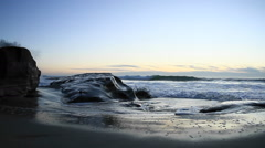 A hand held camera captures waves rolling on to a beach just after sunset. Stock Footage
