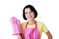 Young housewife in pink apron ang glove Stock Photos