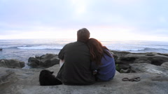 A couple snuggle together on a beach. Stock Footage