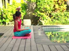 Young woman doing bend exercise on mat in garden by swimming pool  NTSC Stock Footage
