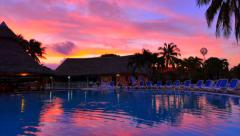 4K Shot of Tropical Purple Sunset over Resort Pool, Reflection and Palm Trees Stock Footage