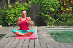 Woman doing breathing exercise sitting on mat in the garden by swimming poo NTSC Stock Footage