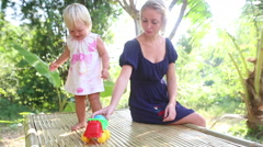 little blonde girl dance near her mother under tropical trees at sunrise - stock footage