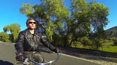 A leather clad man rides a motorized bicycle through the countryside on a two Stock Footage