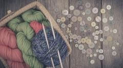 Colorful Yarn and Pastel Buttons On Wood Background - stock photo