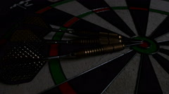 Light sweep effect on a dart board, 3 darts laying and pointing the bull's eye - stock footage