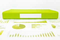 Blank green folder with analytic graph and educational reports - stock photo