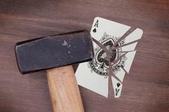 Hammer with a broken card, ace of spades - stock photo