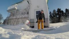 Super slow motion of guy shovelling snow over camera Stock Footage