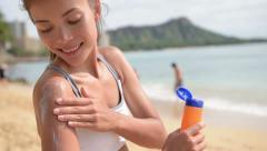 Sunscreen fitness woman applying suntan lotion cream before sport on beach Stock Footage