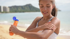 Fitness woman applying sunscreen suntan lotion cream for sun protection Stock Footage