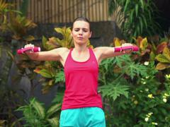 Young, beautiful woman exercising with dumbbells in the garden NTSC Stock Footage