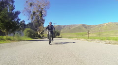 A man rides a motorized bicycle through the countryside on a two lane road. Stock Footage