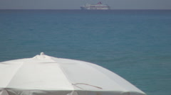 White umbrella on the beach and a boat in background on Mediterranean sea. - stock footage