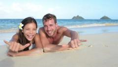Hawaii vacation couple having fun on beach Stock Footage