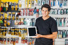 Man Displaying Digital Tablet In Hardware Store - stock photo