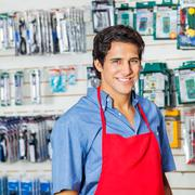 Handsome Worker In Red Apron Smiling At Hardware Shop - stock photo