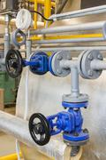 Pipes and faucet valves of heating system in a boiler room - stock photo