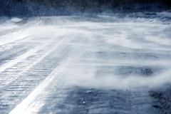 Icy Road with Drifting Snow Closeup. Dangerous Icy Road Conditions. Stock Photos