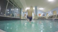 Slow motion overhead child jumping in to pool Stock Footage