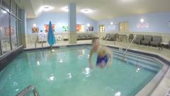 Slow motion child jumping in to indoor hotel swimming pool Stock Footage