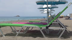 Touristic beach in Mediterranean island, colorful umbrellas and sunbeds. Stock Footage