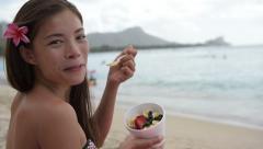 Acai bowl - woman eating healthy food on beach on Hawaii Stock Footage