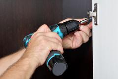 Master of furniture assembly, screwing cordless screwdriver screw, door hinge - stock photo