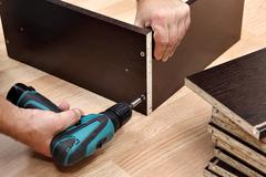 Furniture assembly using a cordless screwdriver, close up. - stock photo