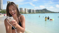 Woman using mobile cell smart phone laughing beach each wearing earphones Stock Footage