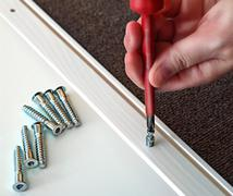Hand with Phillips screwdriver and screws, furniture assembled. Stock Photos