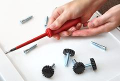 Hands screwed in a furniture panel plug with screw, with a red, cross-shaped Stock Photos