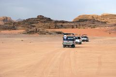 cars of tourists in search of adventures in the desert - stock photo
