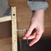 Furniture assembly, wood screw screwed  manually using allen key. Stock Photos