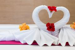 white swans made from towels on bed in the hotel - stock photo