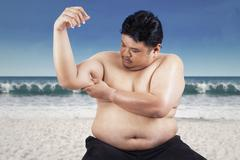 Fat man holding his flabby biceps - stock photo