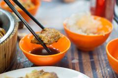 Fried spring roll held by chopticks at a Hong Kong dai pai dong - stock photo